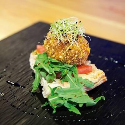 ostada de pan de cristal con un chorro de aceite DOP Siurana con falso tataki de sandía con bomba de carne rellena de salsa de queso cheddar y rebozada con maíz tostado y especiado.