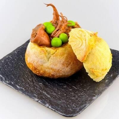 Clotxeta farcida amb ragout de llonganissa d'Alforja, calamars i pèsols acompanyat de salsa japonesa sukiyaki.