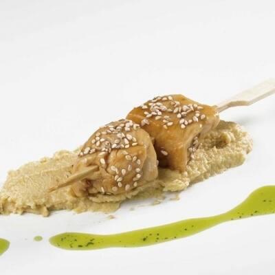 Pincho de pollo sobre lecho de hummus aliñado con aceite de albahaca y semillas