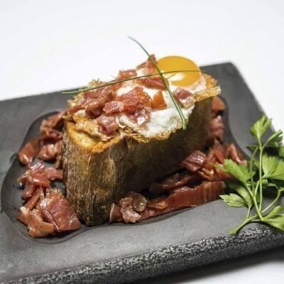 Barquita con foie, huevo de codorniz y virutas de ibérico a las finas hierbas