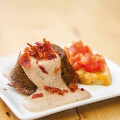 Flam de truita de patata, amb una cremosa salsa de ceps de temporada amb un cruixent de pernil ibèric, acompanyat d'una llesqueta de pa amb tomaca triturada i amanit amb oli DOP Siurana.