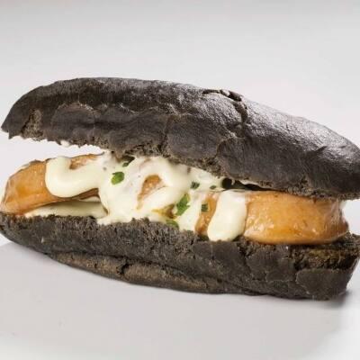 Bocata de calamares estofados con alioli de ajos asados en pan de tinta de calamar y reducción de pescado