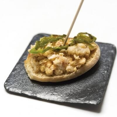 Ous remenats amb bacallà, pebrot i all coronats amb fils de pebrot verd sobre pa d'Antequera.