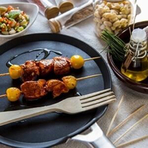 Brochetas de pollo adobado junto a ensalada de pochas