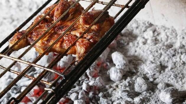 Calentar la brasa a fuego bajo. Hacer el pollo entre 25 y 30 minutos, girándolo a la mitad, y untándolo con algo de la marinada sobrante a mitad de cocción.