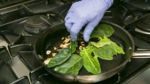 Para las espinacas a la catalana, doramos el ajo en una sartén con un poco de aceite, y añadimos las pasas y los piñones.