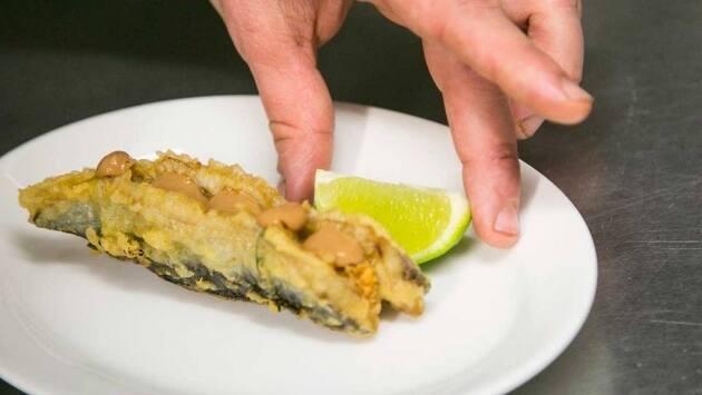 Rallamos un poco de piel de lima sobre las sardinas y las acompañamos con un trocito de lima para aportar acidez al escurrirla justo antes de comerla.