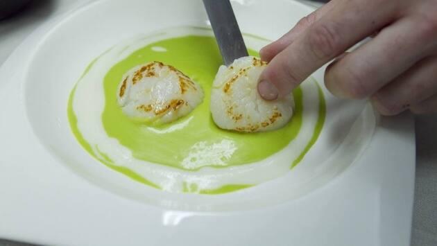 Emplatar el puré de guisante con unas gotas de puré de almendra, las vieiras y los guisantes lágrima encima.