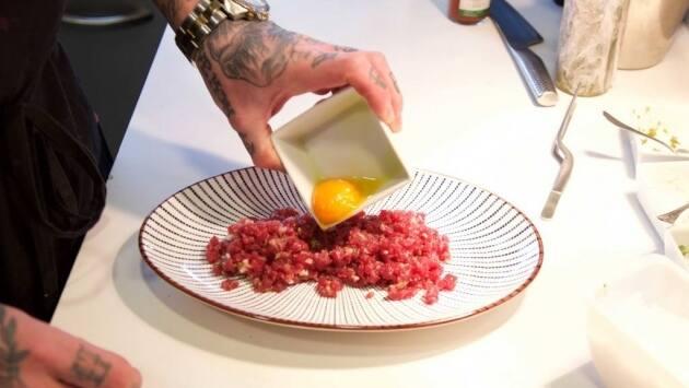 Terminar emplatando el tartar de atún con la yema de huevo en el centro