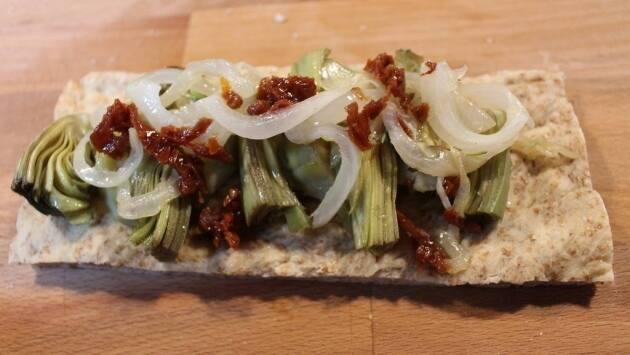 Coca salada con alcachofas, tomate seco y queso fresco