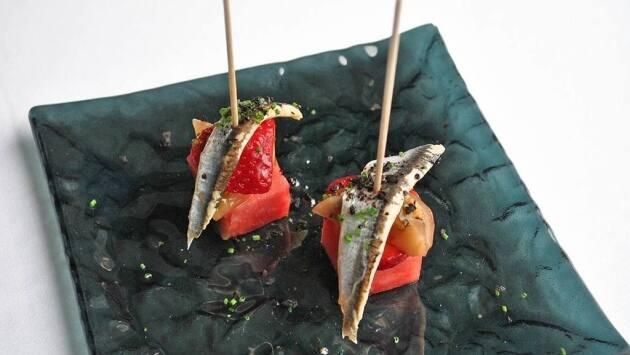 Brocheta de sandía marinada con vinagre de frambuesa, tomate kumato y boquerón.